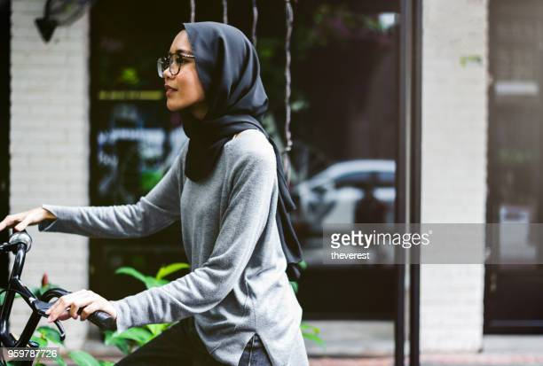 pretty malaysian girl riding her bicycle - modest clothing stock pictures, royalty-free photos & images