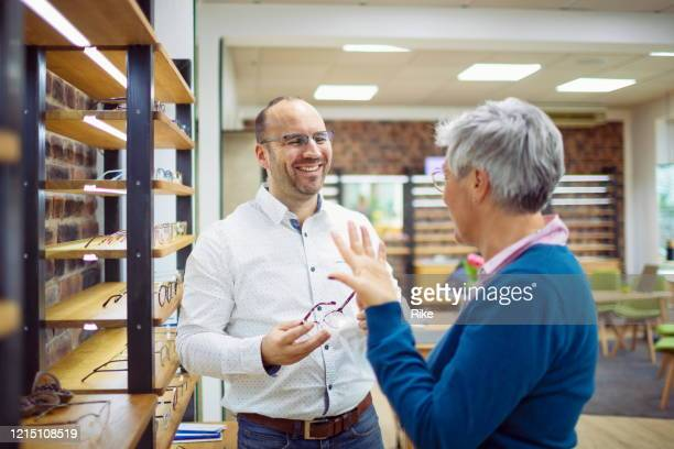 pretty mature customer gets advice from the optician in the shop - german short haired pointer stock pictures, royalty-free photos & images