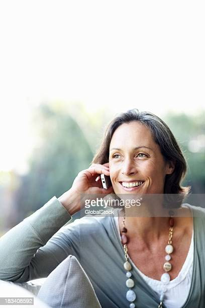 Hübsche, ältere Frau, die ein Gespräch am Telefon