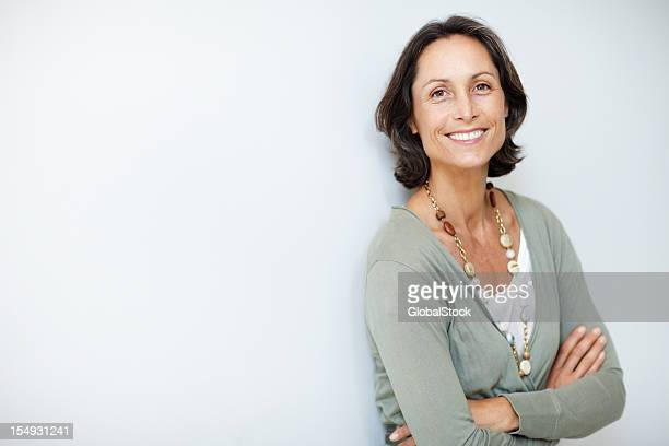 pretty, mature woman standing with her hands folded - brown hair stock pictures, royalty-free photos & images