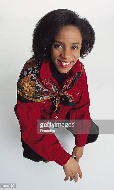 pretty middle aged african american adult female wearing a red blouse with a scarf over her shoulders kneels down while smiling up at the camera pleasantly - down blouse stock-fotos und bilder