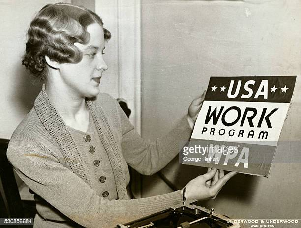 Pretty Miss Louise Hasley, of the staff of the Works Progress Administration at Washington, examining one of the new WPA official posters which will...