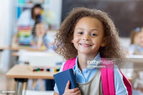 Pretty mixed race girl in preschool classroom