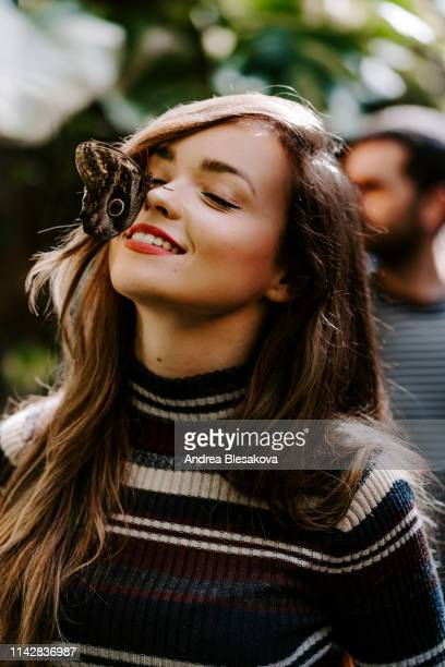pretty model girl with butterfly sitting on her - botanischer garten stock-fotos und bilder