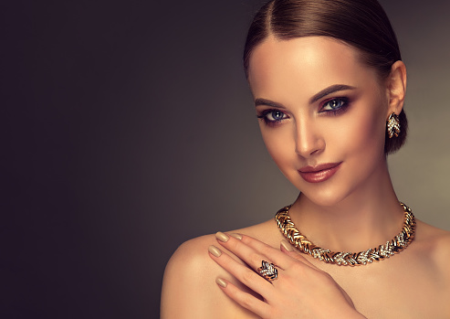 Pretty model with smoky-eyes makeup style is demonstrating gilded jewelry set. 968313042