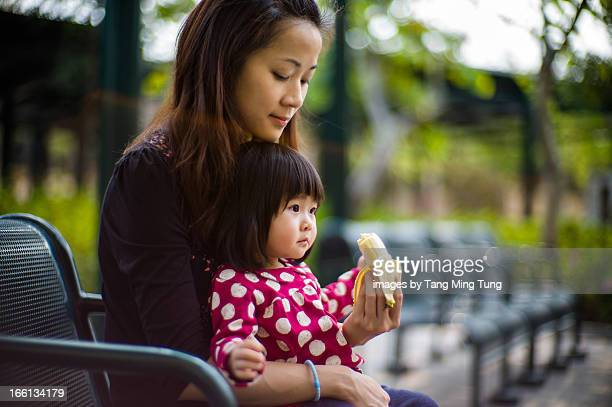 Pretty mom having banana with toddler on a bench