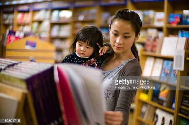 Pretty mom holding baby choose books in bookstore