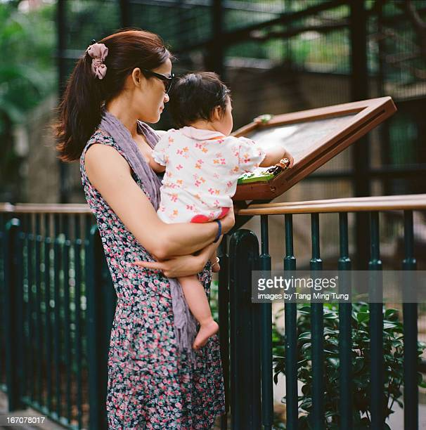 Pretty mom holding baby visiting a zoo