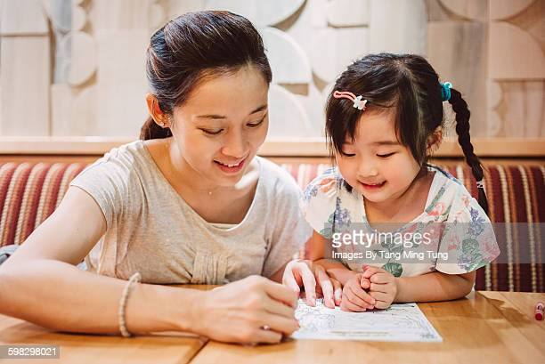 Pretty mom & little daughter drawing in restaurant