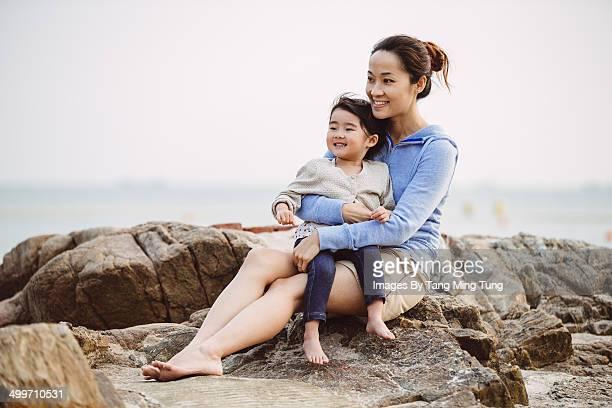 Pretty mom & little girl sitting on rocky shore