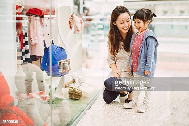 Pretty mom shopping with little daughter joyfully