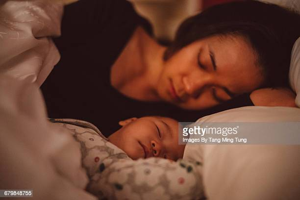 Pretty mom sleeping soundly with baby at night