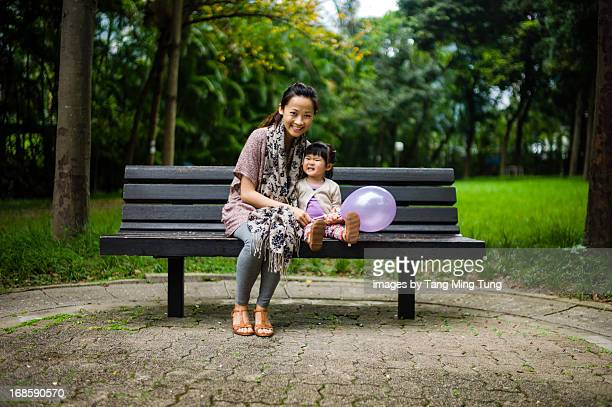 Pretty mom & toddler sitting on bench smiling