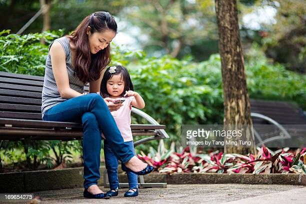 Pretty mom & toddler using smartphone in the park