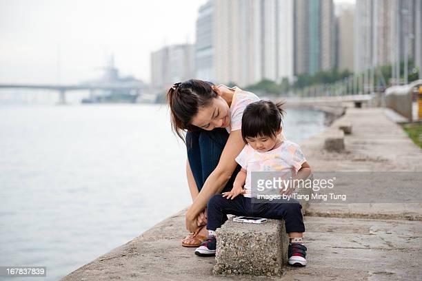 Pretty mom & toddler using smartphone joyfully