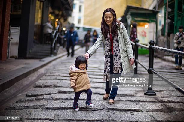 Pretty mom walking down stairs with baby joyfully