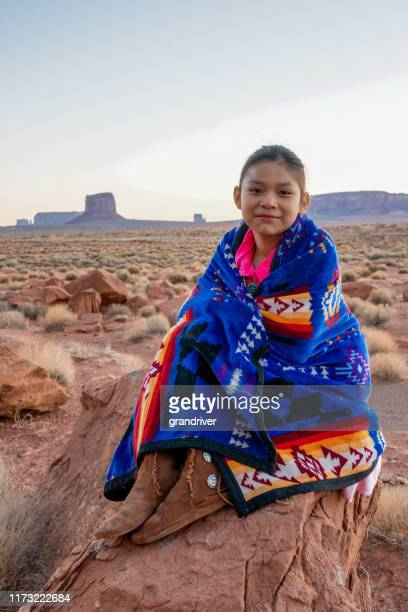 pretty nine year old native american navajo indian girl in the early morning hours dressed in traditional clothing posing in front of the monument valley tribal park - apache stock pictures, royalty-free photos & images