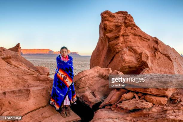 pretty nine year old native american navajo indian girl in the early morning hours dressed in traditional clothing posing in front of the monument valley tribal park - apache indian stock pictures, royalty-free photos & images