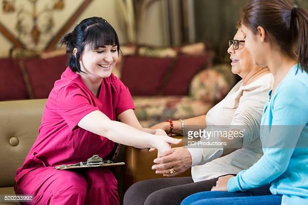 Pretty nurse checks senior female patient's arm