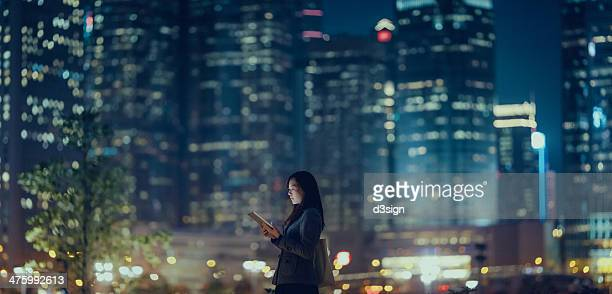 Pretty office lady is using tablet in city