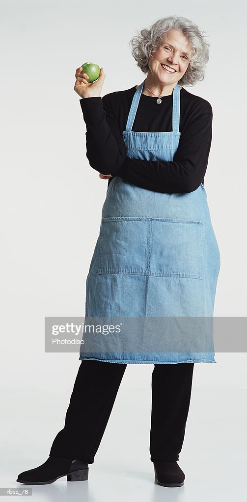 pretty old caucasian adult female white hair wears dark pants shirt blue apron stands holds apple : Foto de stock