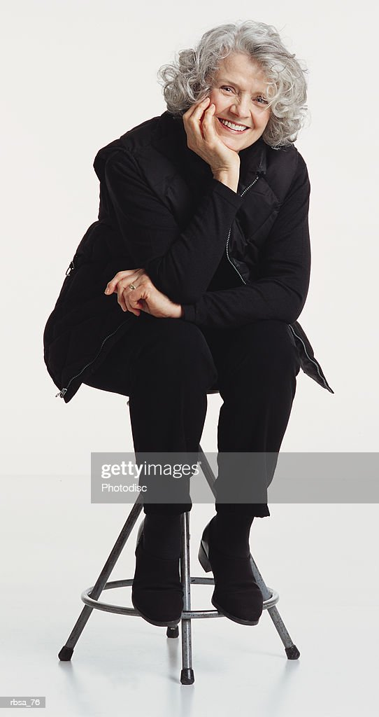 pretty old caucasian adult female with curly gray hair wearing a dark vest and dark pants sitting on a stool as she leans forward resting her chin in her hand and smiles at the camera : Foto de stock
