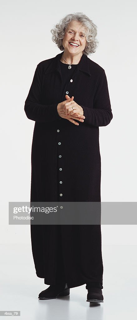 pretty old caucasian adult female with curly gray hair wearing a long dark trendy dress while standing with hands clasped and smiling at the camera : Foto de stock