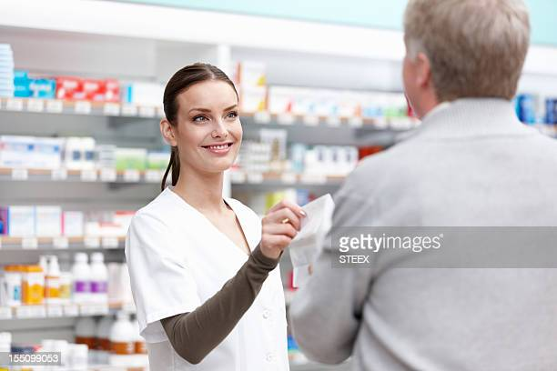 Pretty pharmacist giving a package