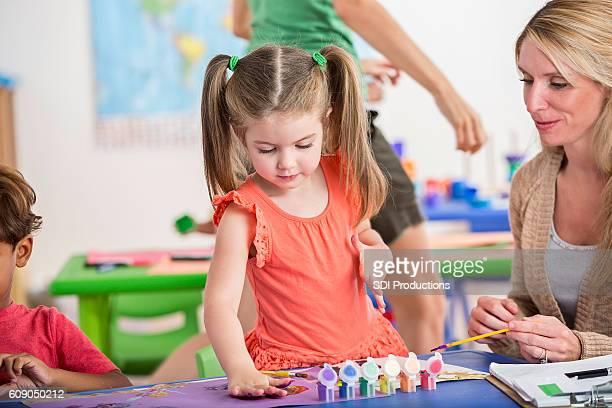 Pretty preschool girl and her teacher work on painting