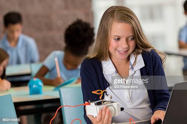 Pretty preteen girl programming robot in STEM education class