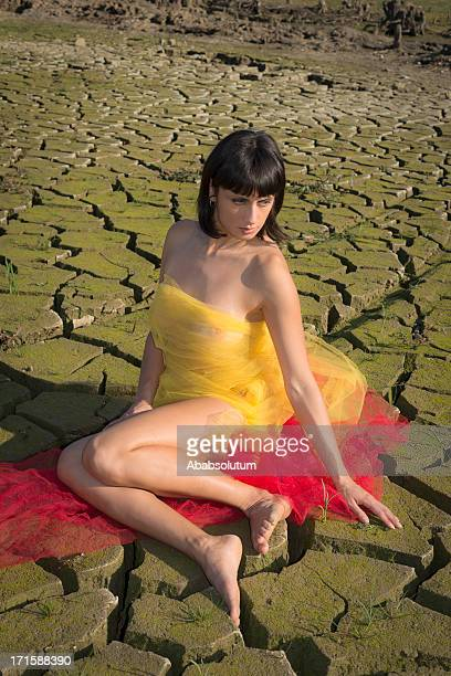 Pretty Seminude Brunette in Red and Yellow, Cracked Earth,Europe