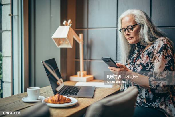 pretty senior woman multi-tasking at coffee shop - white hair stock pictures, royalty-free photos & images