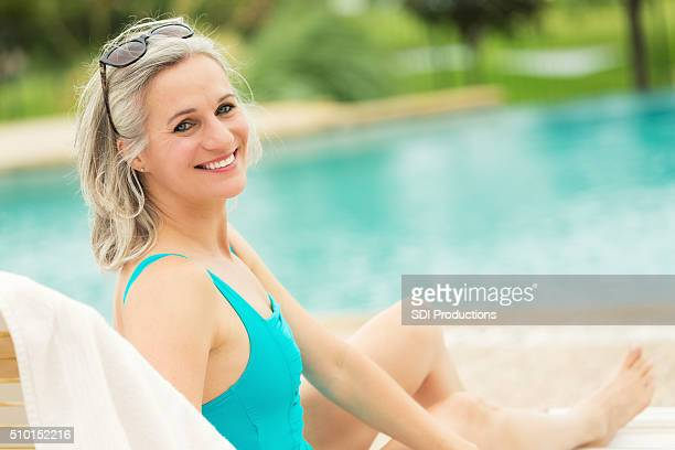 pretty senior woman relaxes beside swimming pool - next to stock pictures, royalty-free photos & images