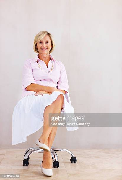 pretty senior woman relaxing in chair - cross legged stock pictures, royalty-free photos & images