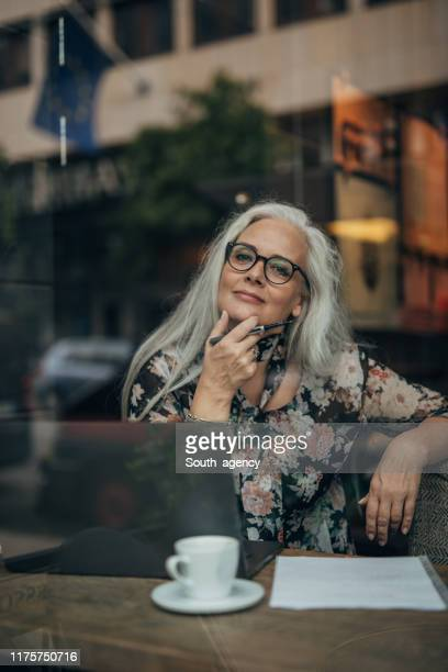 pretty senior woman working on laptop - long hair stock pictures, royalty-free photos & images