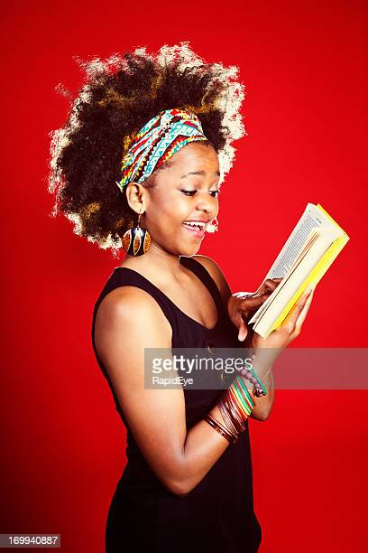 Pretty, smiling, afro-haired woman reading book against red background
