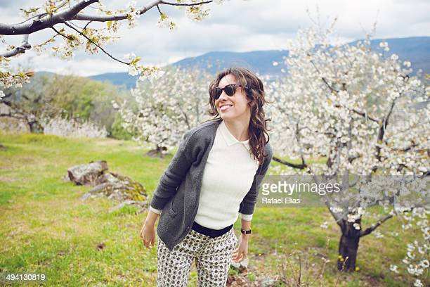 Pretty smiling woman and blossoming cherry trees