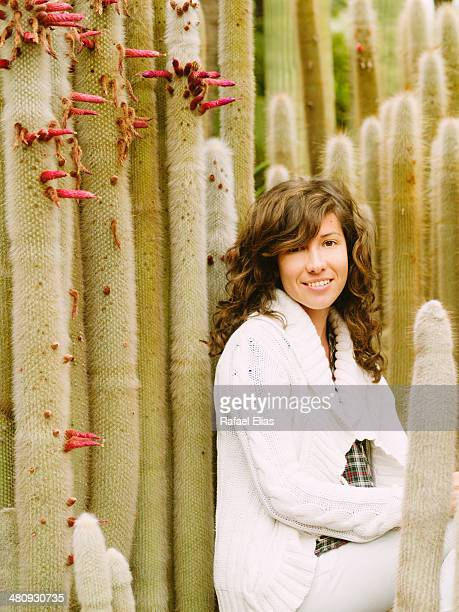 Pretty smiling woman in cactus garden