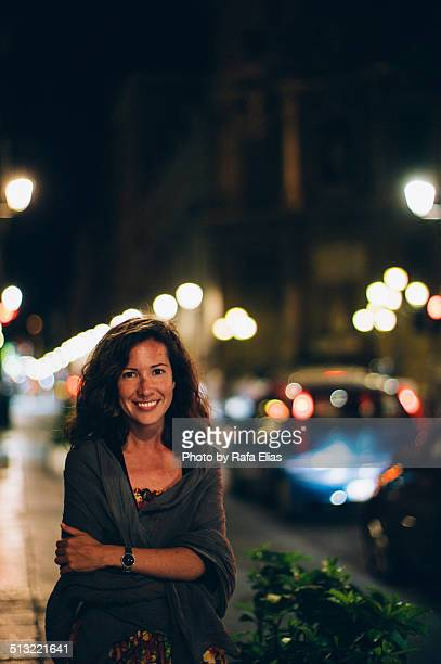 pretty smiling woman in the street at night - one mid adult woman only stock pictures, royalty-free photos & images