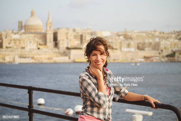 pretty smiling woman leaning against handrail by the sea in valletta (malta) - valletta stock pictures, royalty-free photos & images