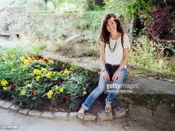 Pretty smiling woman sitting in garden