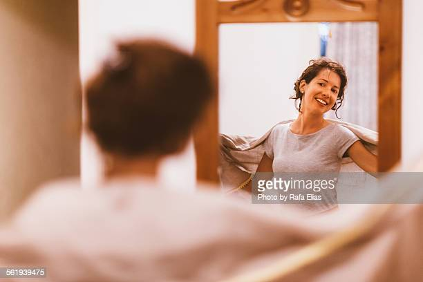 Pretty smiling woman with shawl looking in mirror