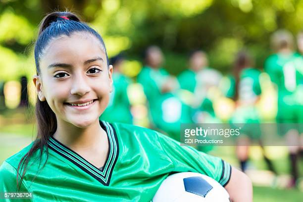 Pretty soccer player holding the ball with her team