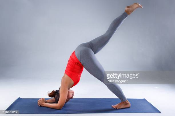 pretty sporty indian woman practicing difficult yoga pose in a concrete background, - yoga pants stock photos and pictures