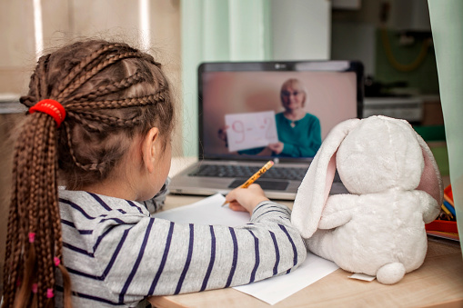Pretty stylish schoolgirl studying math during her online lesson at home, self-isolation 1214106771