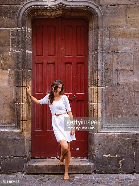 Pretty stylish young woman standing at red door