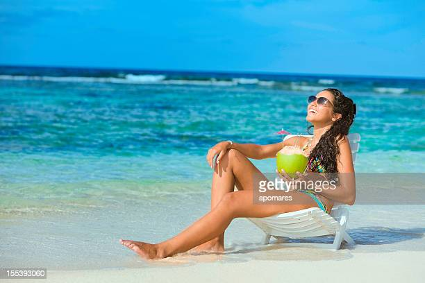 Pretty tanned young woman relaxing on Caribbean beach