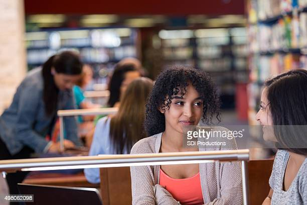 Pretty teen girl taking to friend while studying in library