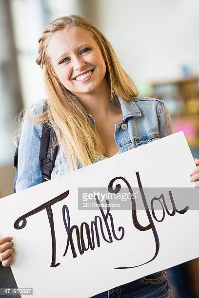 Pretty teen high school student holding ''thank you'' sign
