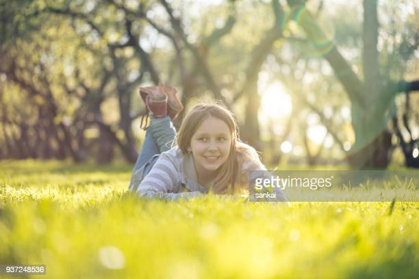 pretty teenage girl laying on a grass - petite teen girl stock photos and pictures